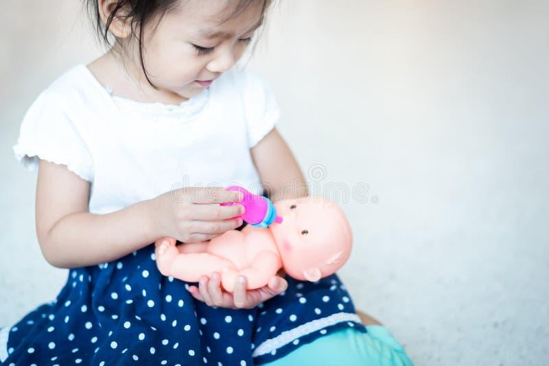 Süßes asiatisches kleines Babykind, das Puppe, Saugflaschemilch zum Baby - Puppe spielt stockfoto