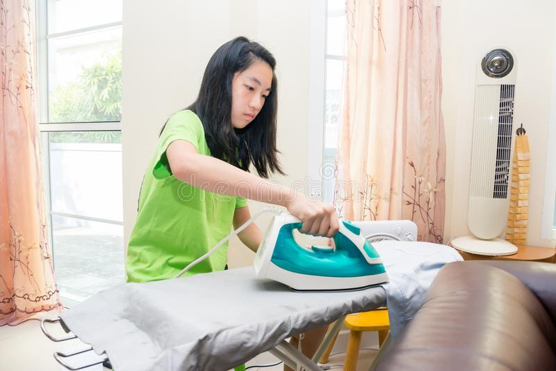 Süßes asiatisches Mädchen, das den Stoff bügelt stockfotos