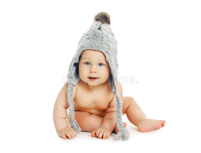Süßes Baby, das in der grauen Strickmütze sitzt lizenzfreies stockfoto