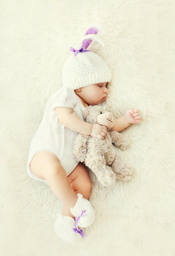 Süßes Baby, das mit Teddybärspielzeug auf weißem weichem Betthaus schläft stockfotografie