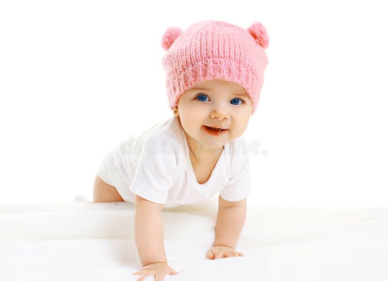 Süßes Baby kriecht in die rosa Strickmütze stockfoto
