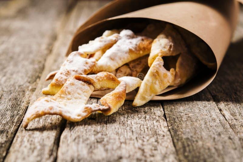 Süßes dünnes knusperiges frittiertes Plätzchen ` Reisig ` überstieg mit Puderzucker in den Papiertüten stockbilder