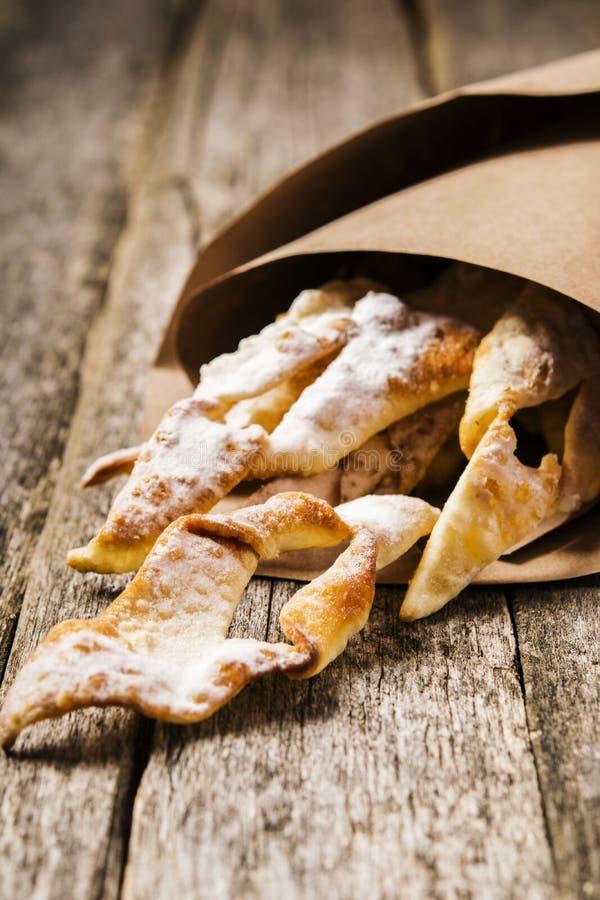 Süßes dünnes knusperiges frittiertes Plätzchen ` Reisig ` überstieg mit Puderzucker in den Papiertüten lizenzfreie stockbilder