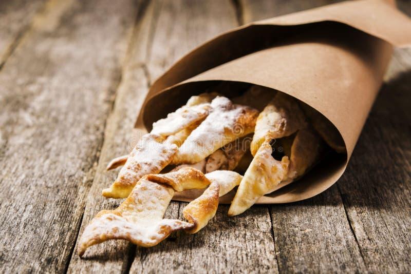 Süßes dünnes knusperiges frittiertes Plätzchen ` Reisig ` überstieg mit Puderzucker in den Papiertüten lizenzfreies stockbild