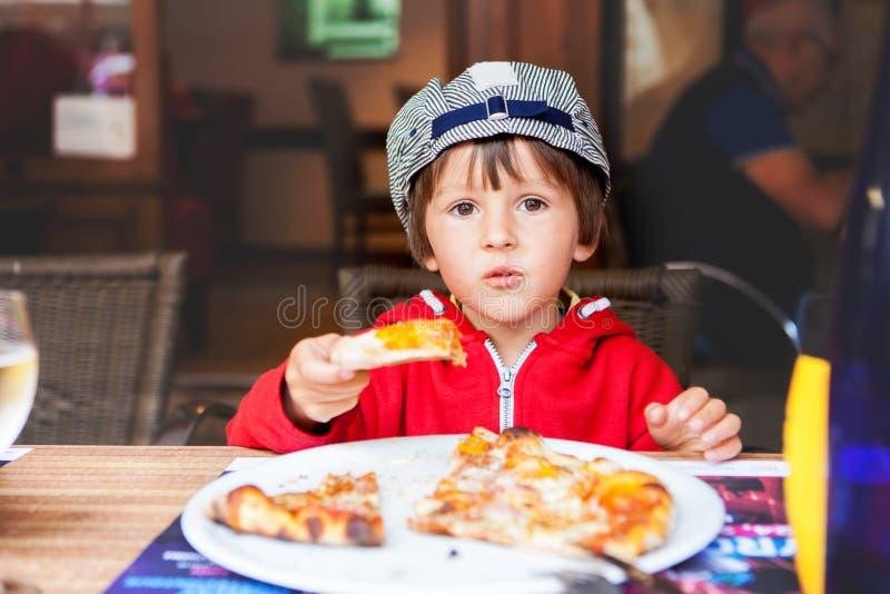 Süßes entzückendes Kind, Junge, Pizza an einem Restaurant essend stockfotografie