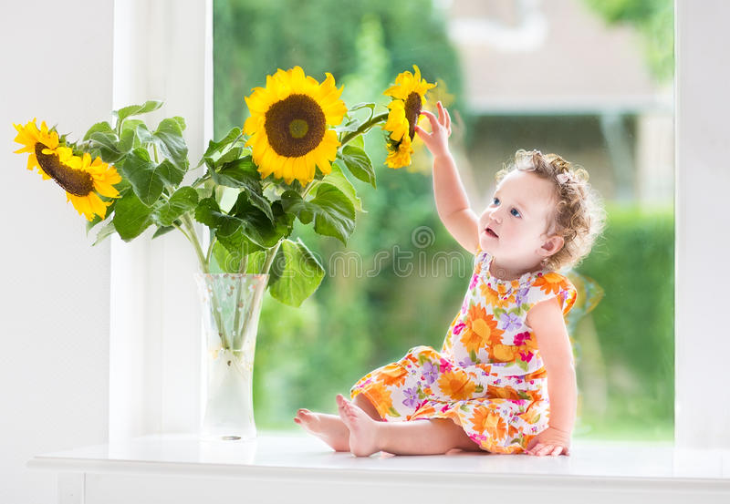 Süßes gelocktes Baby nahe bei Sonnenblumenblumenstrauß stockbilder