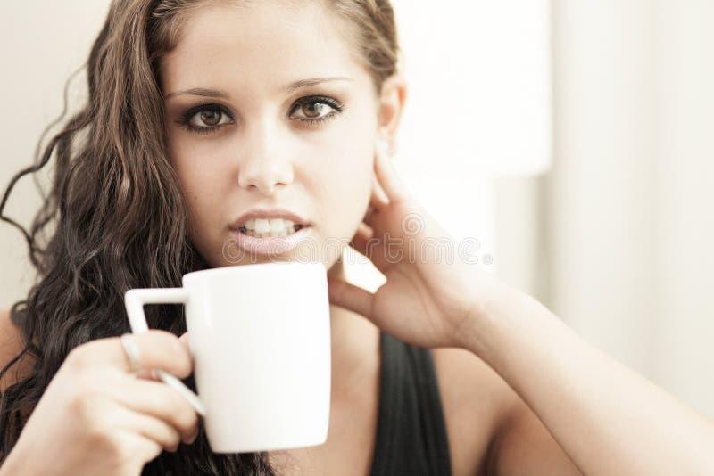 Süßes Hörnchen und ein Tasse Kaffee im Hintergrund stockbilder