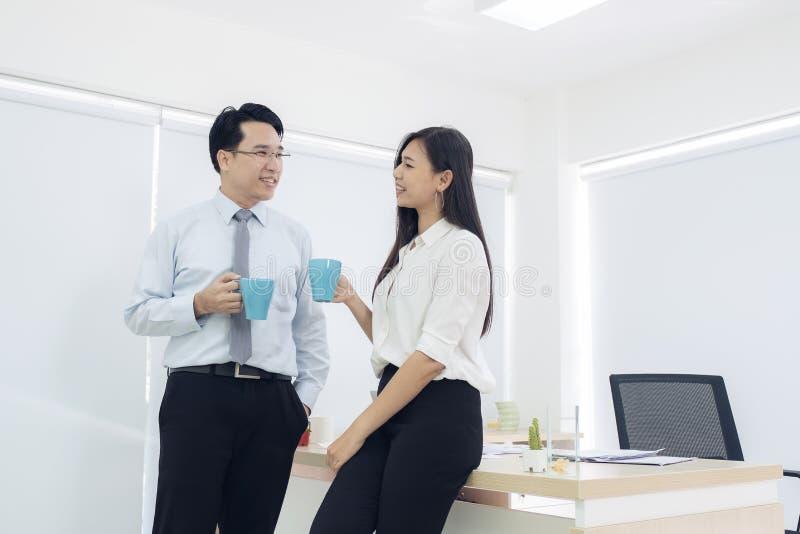 Süßes Hörnchen und ein Tasse Kaffee im Hintergrund Paare von jungen Kollegen in der Stellung der formellen Kleidung stockfotos