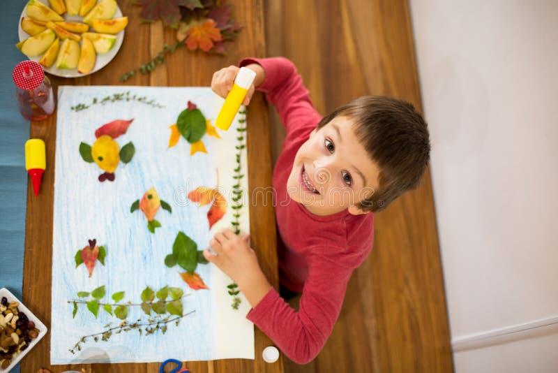 Süßes Kind, der Junge, zutreffend verlässt mit Kleber lizenzfreie stockfotos