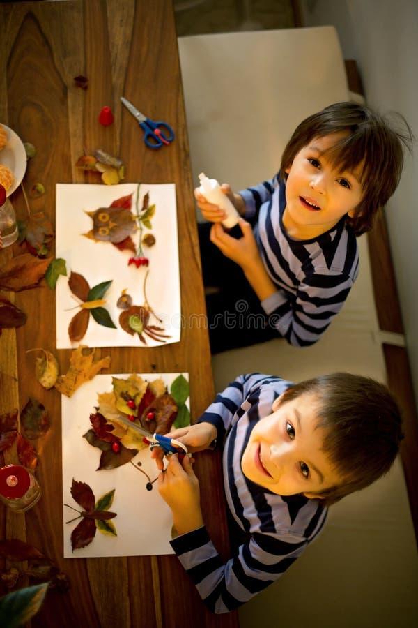 Süßes Kind, der Junge, zutreffend verlässt mit Kleber beim Handeln von den Künsten lizenzfreie stockfotografie
