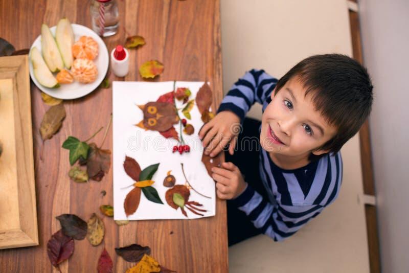 Süßes Kind, der Junge, zutreffend verlässt mit Kleber beim Handeln von den Künsten stockfoto