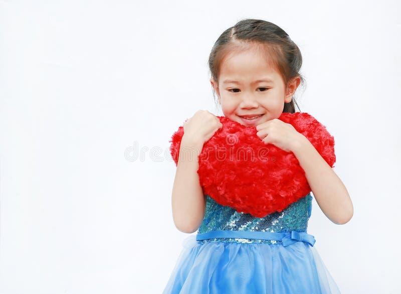 Süßes kleines asiatisches Kindermädchen hält ein rotes Herz der Valentinsgrüße lokalisiert auf weißem Hintergrund stockfoto