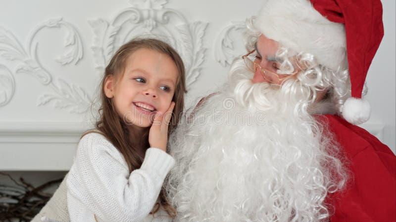Süßes kleines Mädchen auf Santa Claus-Schoss, der ihm sagt, was sie für Weihnachten wünscht stockfotografie