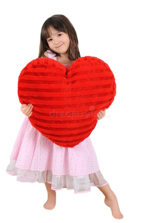 Süßes kleines Mädchen, das großes rotes Innerkissen anhält stockbilder