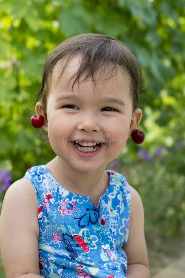 Süßes kleines Mädchen, das mit Kirschohrringen lacht stockbild