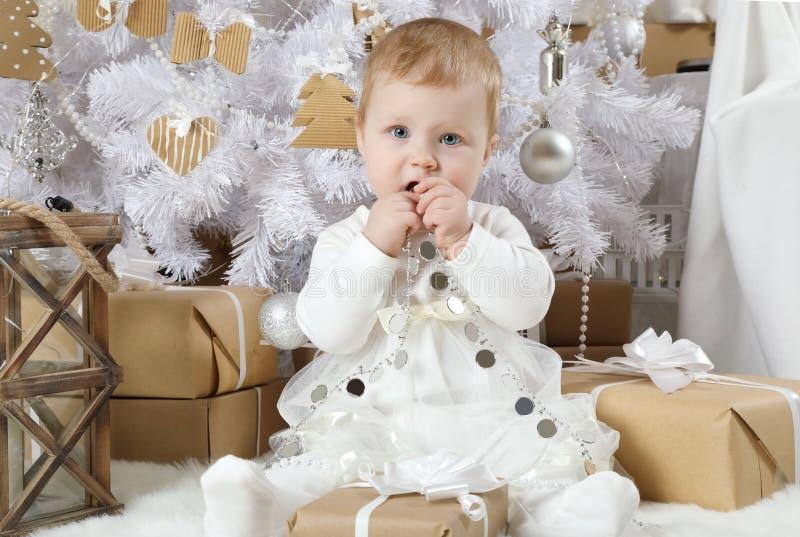 Süßes kleines Mädchen, das unter einem Weihnachtsbaum sitzt lizenzfreies stockfoto