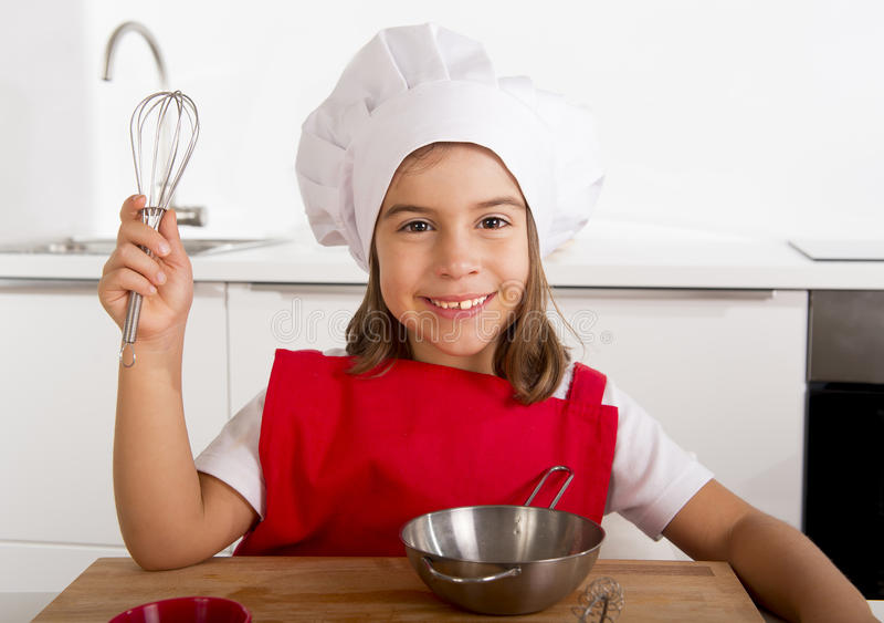Süßes kleines Mädchen im roten Schutzblech- und Kochhut, der den Chef lernt spielt, Küche zu Hause kochend stockbild