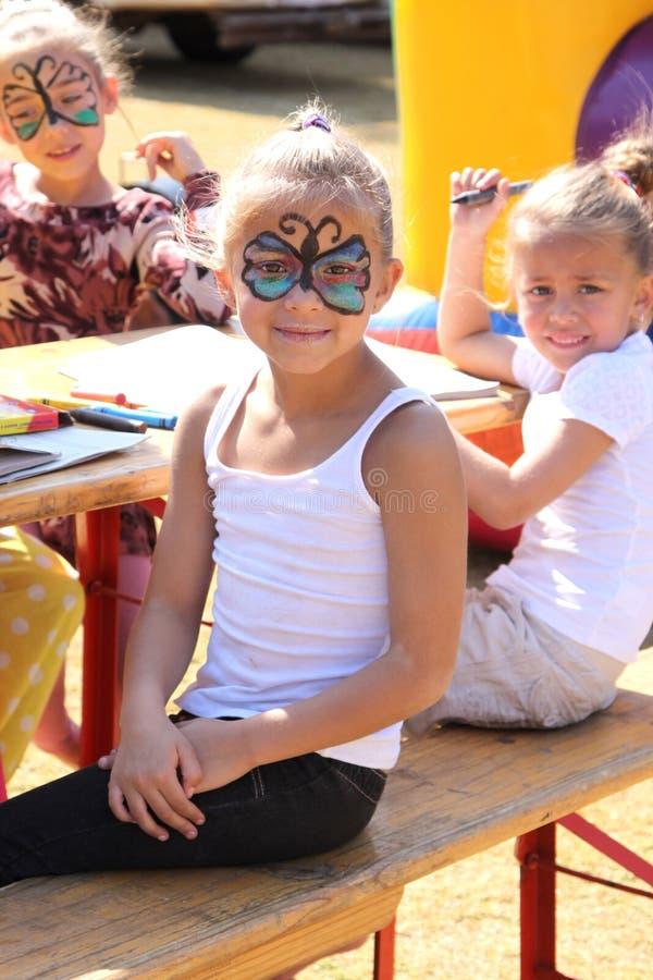 Süßes kleines Mädchen mit Gesichtsfarbe am Festival stockfoto