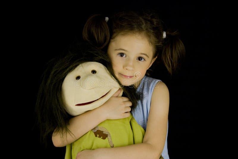 Süßes kleines Mädchen umfaßt ihre Lieblingspuppe stockfoto