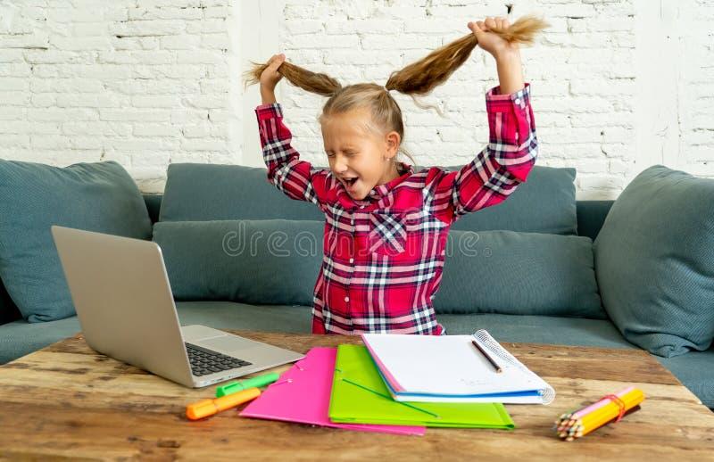 Süßes kleines Volksschulemädchen, das ihr blondes Haar im Druck wird verrückt beim Versuchen zu studieren und Handeln von Hausarb stockbild