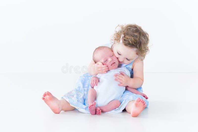 Süßes Kleinkindmädchen, das ihren neugeborenen Babybruder küsst stockfoto