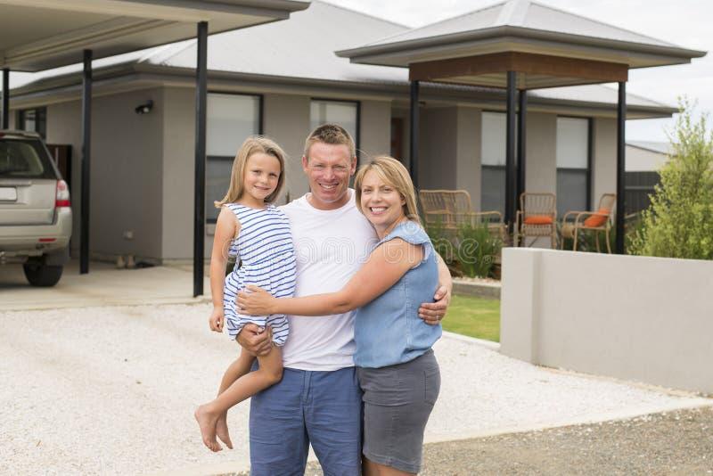 Süßes liebevolles Familienporträt mit dem Ehemann und Frau, welche die schöne kleine Tochter zusammen aufwirft vor modernem Haus  lizenzfreies stockbild