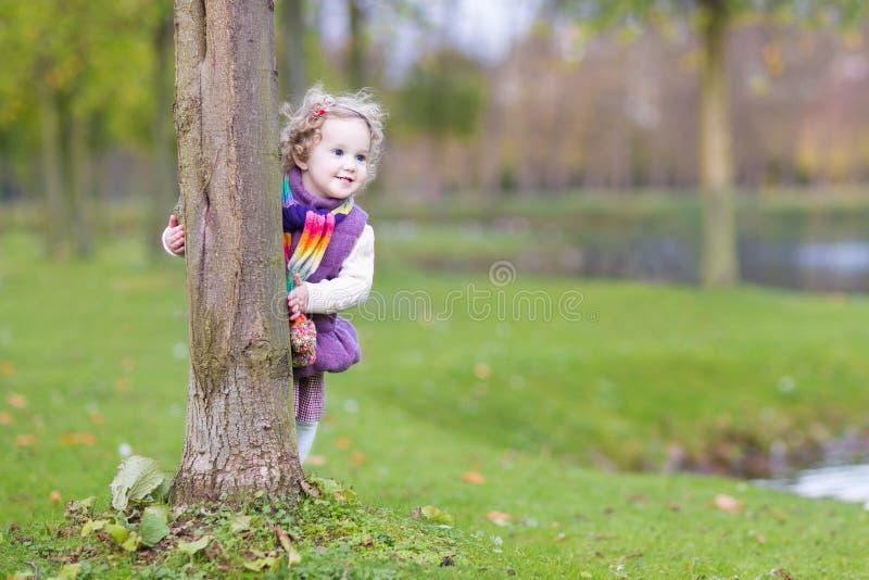Süßes lustiges Kleinkindmädchen, das hinter Baum im Park sich versteckt stockfoto
