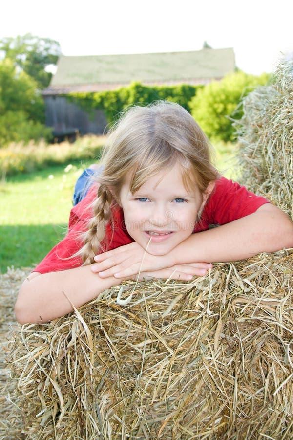 Süßes Mädchen, das auf einen Strohballen legt. stockbild