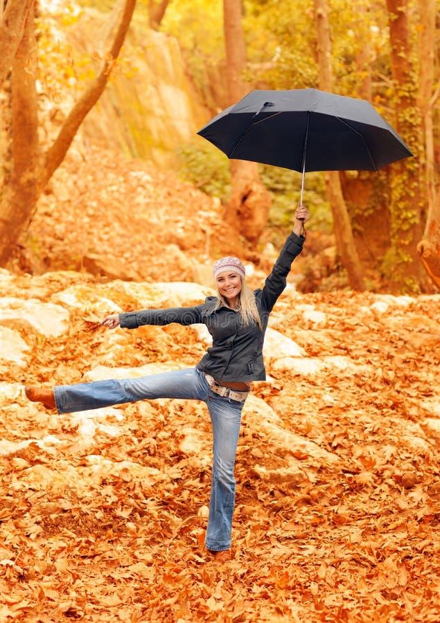 Süßes Mädchen, das mit Regenschirm springt stockbilder