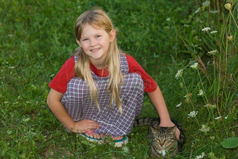 Süßes Mädchen, das nahe bei ihrer Katze im Gras hockt. stockbild