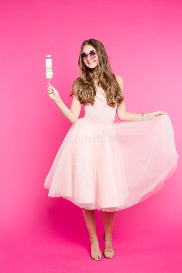 Süßes Mädchen im Kleid wie der Puppe, die mit Eibischsüßigkeit aufwirft stockbilder