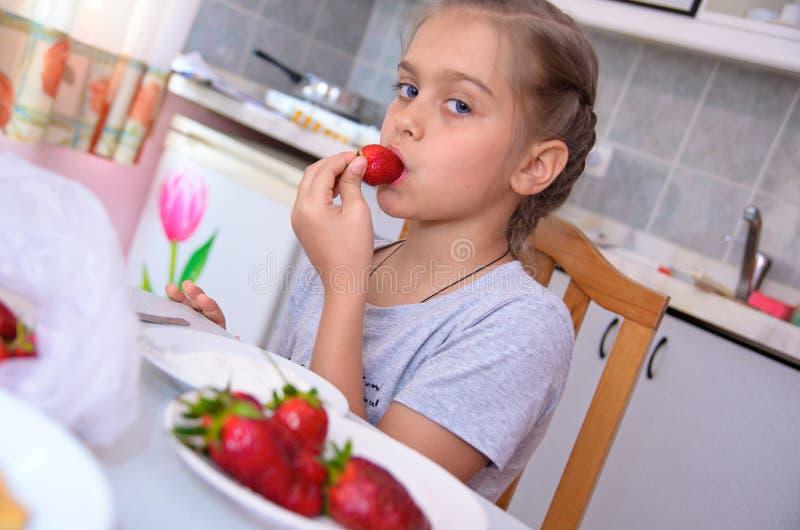 Süßes Mädchen isst Erdbeeren stockfoto
