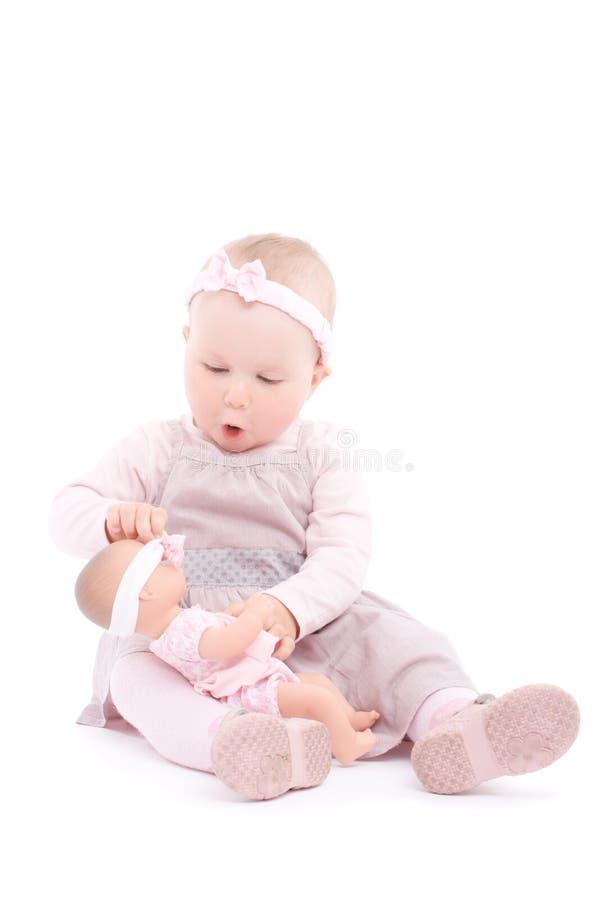 Süßes Spiel des kleinen Mädchens mit Puppe stockbild