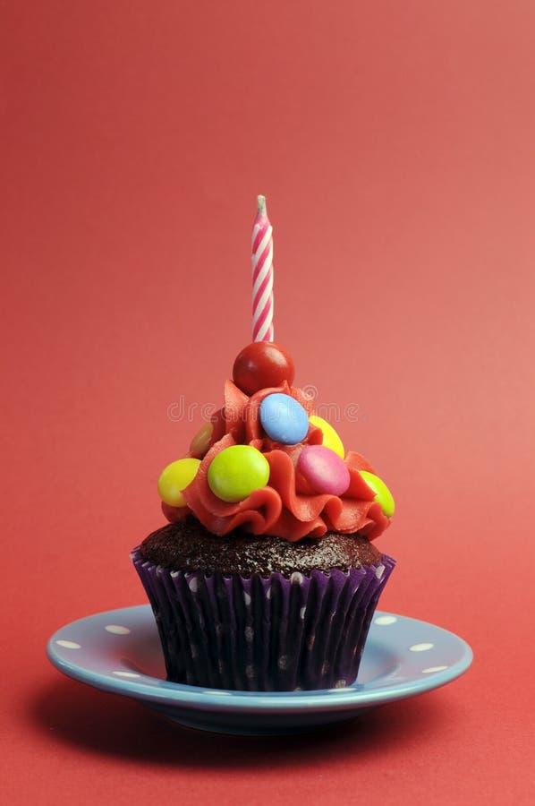 Süßigkeit bedeckte Schokoladenkleinen kuchen mit dem Rotbereifen und Süßigkeit und eine Geburtstagskerze auf rotem Hintergrund stockfotografie