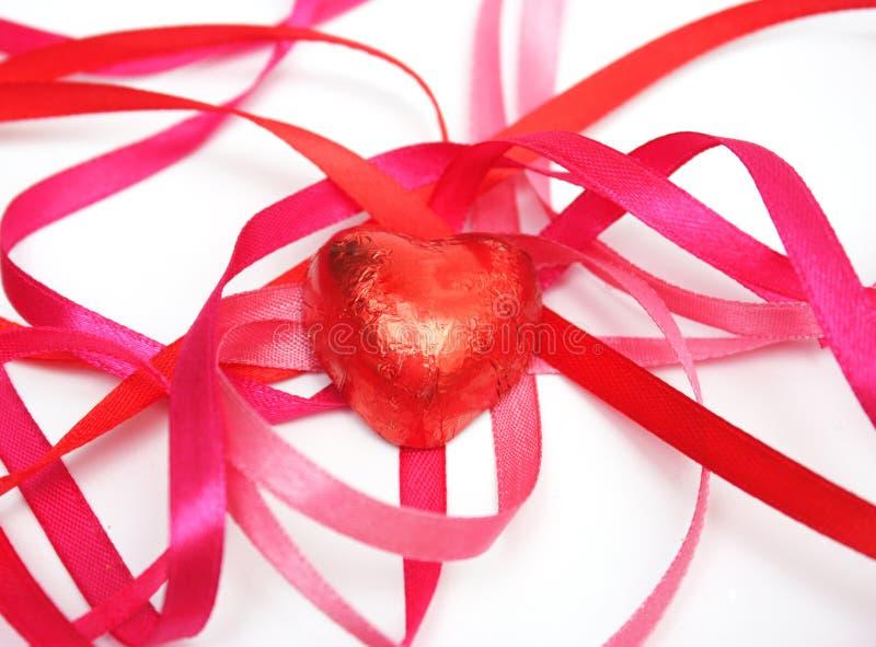 Süßigkeit in der roten Folie und im roten Satinfarbband stockbilder
