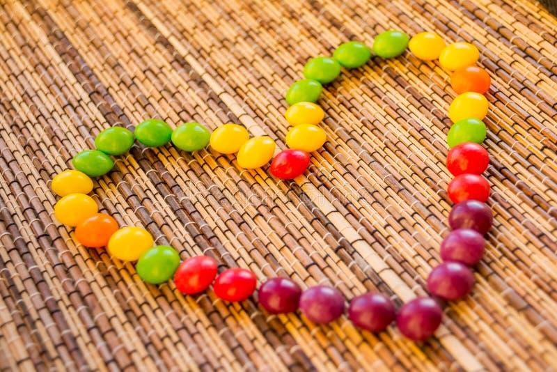 Süßigkeit, die eine Herzform bildet buntes Bonbon auf Strohserviette wie einem Herzen Bambusserviettenmattenbeschaffenheit Hölzer stockbild