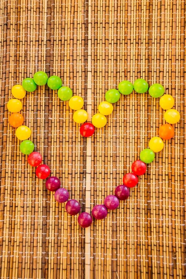 Süßigkeit, die eine Herzform bildet buntes Bonbon auf Strohserviette wie einem Herzen Bambusserviettenmattenbeschaffenheit Hölzer lizenzfreie stockfotos