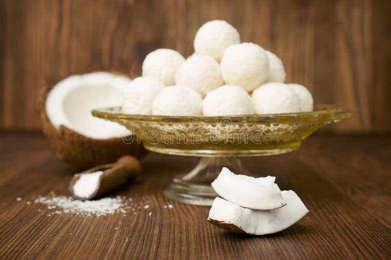 Süßigkeiten in den Kokosnussflocken und in der frischen Kokosnuss stockfotos