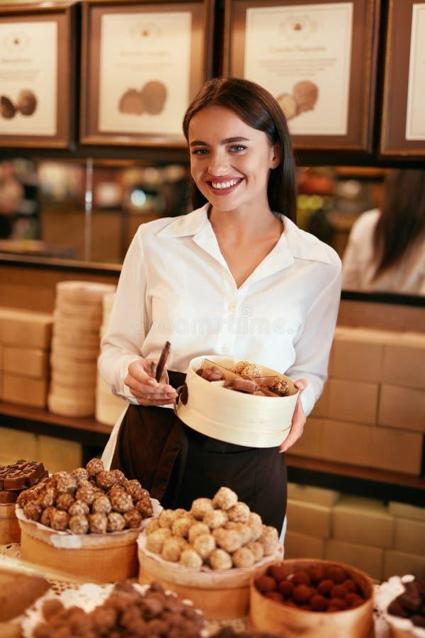 süßigkeiten Frau, die Pralinen im Speicher verkauft stockfotografie