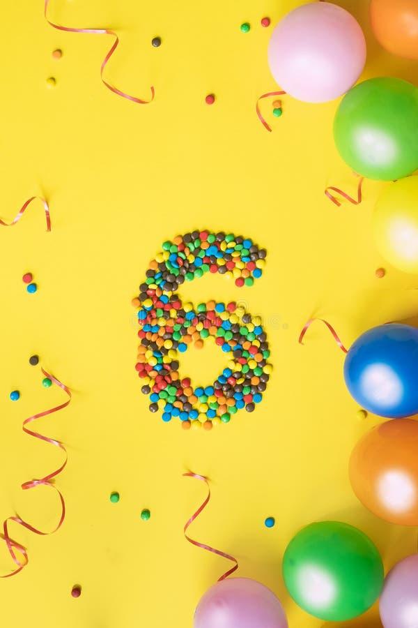 Süßigkeiten nummerieren 6 mit bunten Ballonen auf gelbem Hintergrund Konzept für Geburtstage lizenzfreie stockfotos