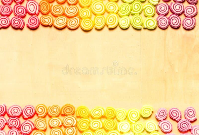 Süßigkeiten und bunte Bonbons der Gelees auf hölzernem Hintergrund lizenzfreie stockfotografie