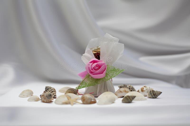 Süßigkeitgeschenk mit Shell auf silk Hintergrund lizenzfreie stockfotos