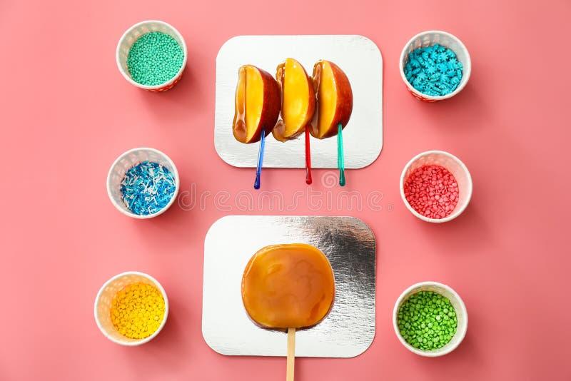 Süßigkeitsapfelkeile mit unterschiedlichem besprüht auf Farbhintergrund lizenzfreie stockfotos