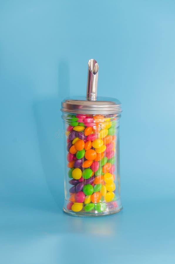 Süßigkeitskaramel in der Zuckerschüssel, Abschluss- oben auf blauem Hintergrund lizenzfreie stockbilder
