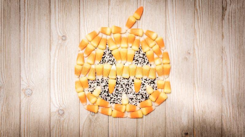 Süßigkeitsmais bildet ein Laternenkürbis der Steckfassung O 'auf Holz lizenzfreies stockbild