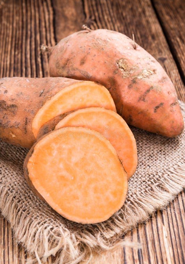 Süßkartoffel (ungekocht) auf hölzernem Hintergrund lizenzfreies stockfoto