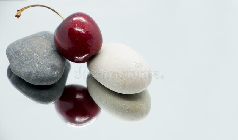 Süßkirsche und Steine auf der Spiegelfläche stockfotos