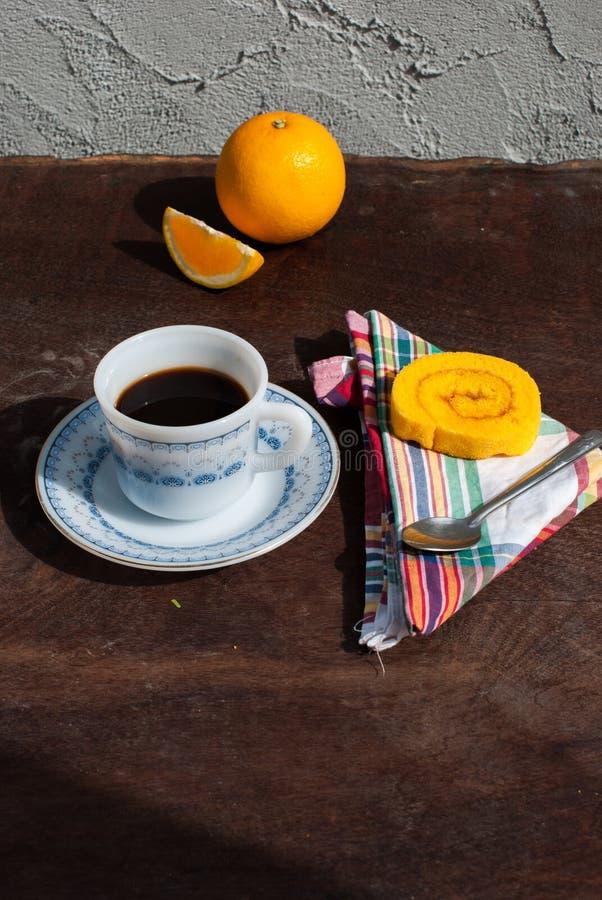 Süßorangestaurollenkuchen mit Kaffee stockfotografie