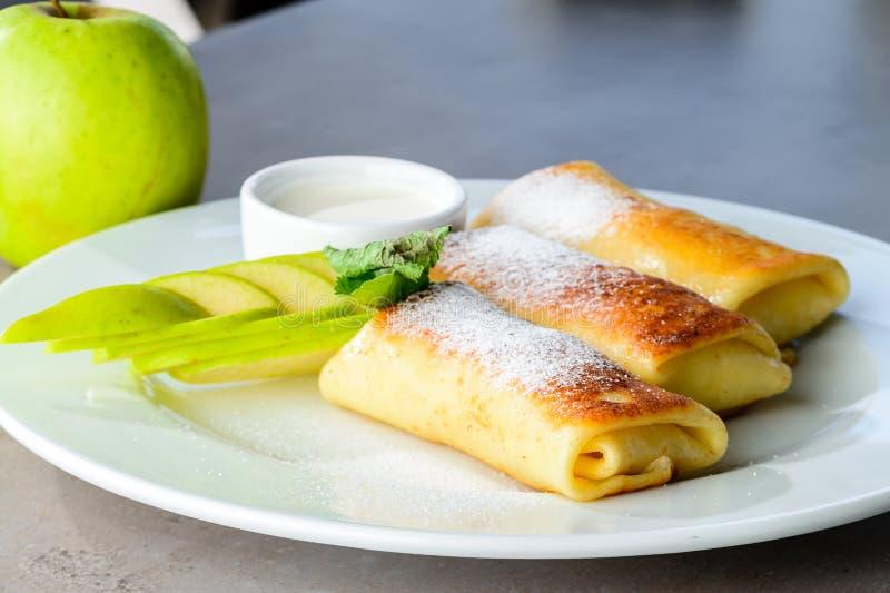 Süßspeisepfannkuchen mit Äpfeln und Puderzucker O lizenzfreie stockbilder