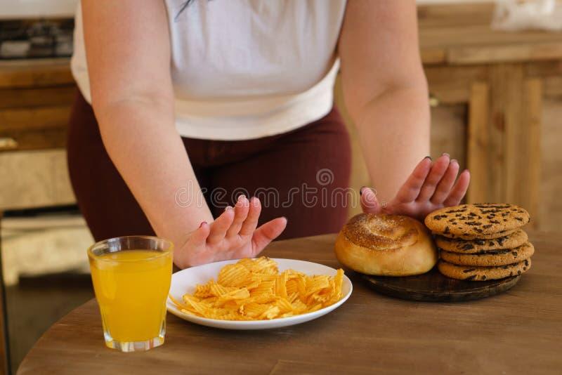 Süchtiger Frauenabfall, zum von Bonbons und von ungesunder Fertigkost zu essen lizenzfreie stockfotografie